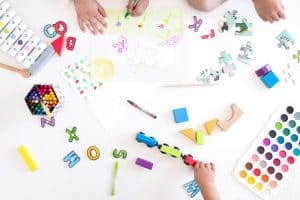 birds eye view of children hands playing with toys and arts and crafts on white flooring