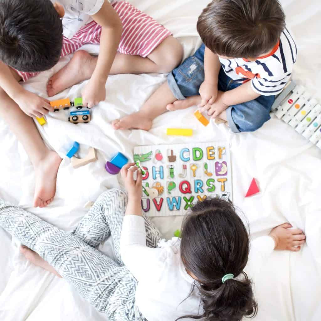 birds eye view of three children playing on a bed with puzzles and toys