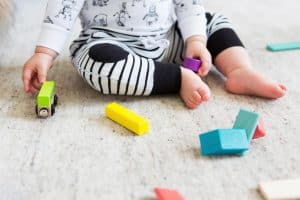 baby from te belly down on the floor sitting up playing with colorful wooden shape blocks