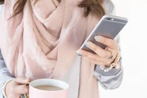 female no face shown holding a mug with coffee and a silver smart phone