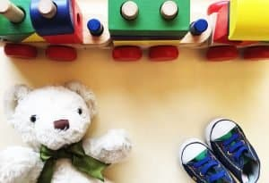 birds eye view of children toy colorful wooden train, teddy bear and baby shoes on floor