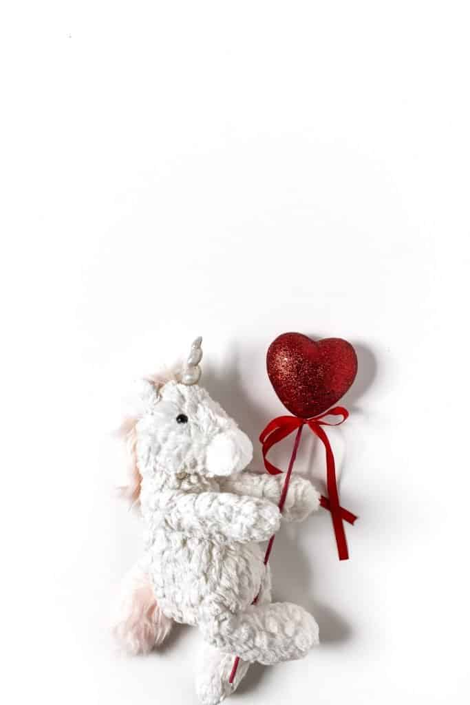 birds eye view of a plush toy unicorn holding a small red heart ballon