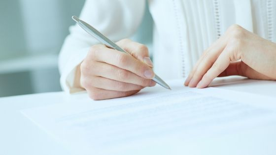white woman signing a paper